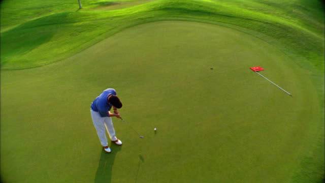 a golfer successfully makes a putt on a green. - golf stock-videos und b-roll-filmmaterial