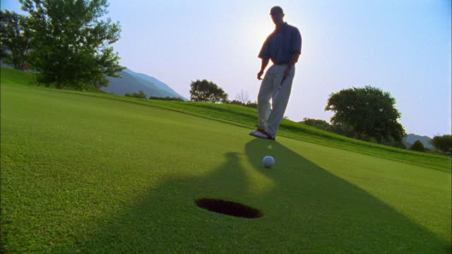 vídeos y material grabado en eventos de stock de a golfer successfully makes a putt on a green. - putt