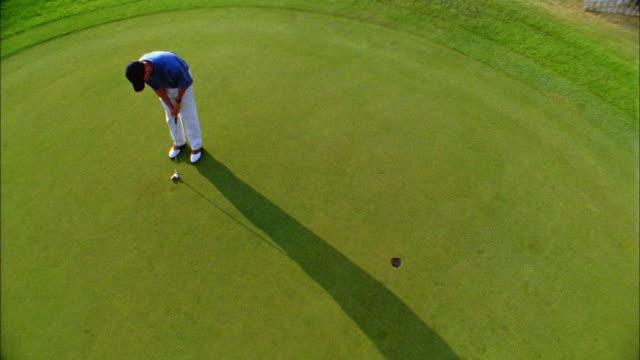 vidéos et rushes de a golfer successfully makes a putt on a green. - putt