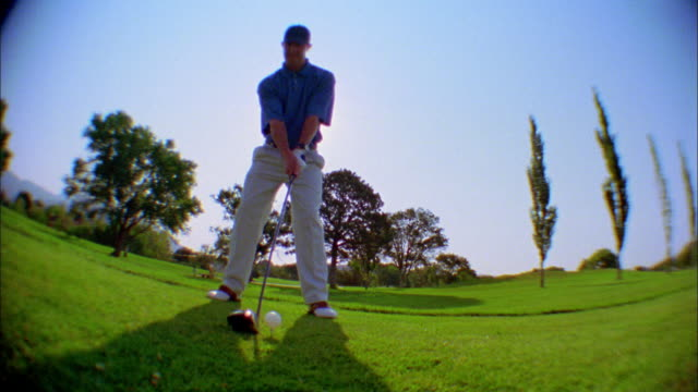 a golfer swings and hits a golfball. - golf swing stock videos & royalty-free footage