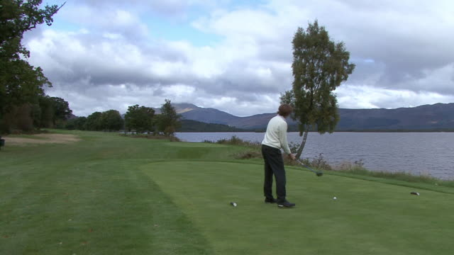 vidéos et rushes de ws golfer teeing off at loch lomond golf course / scotland, united kingdom - tee off