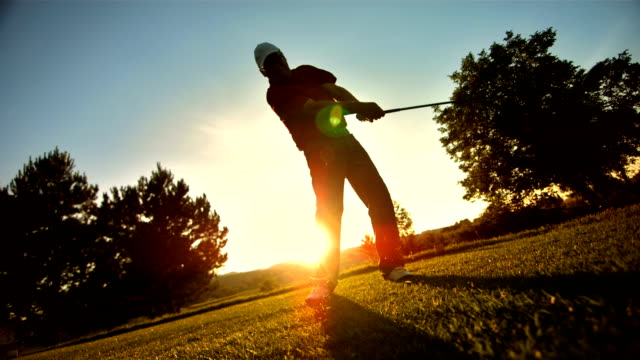 slo mo ws pan golfer teeing off at sunset - golf ball stock videos & royalty-free footage