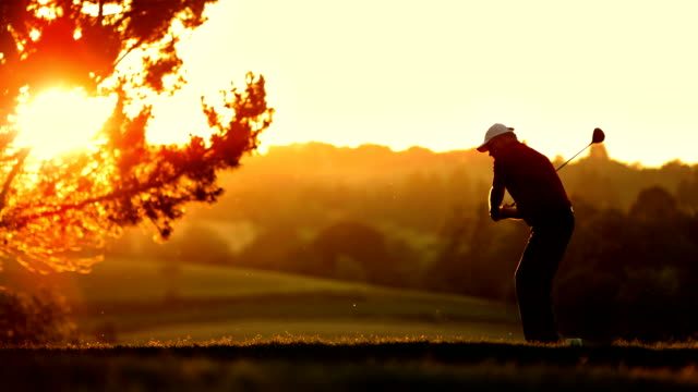 slo mo ws golfer teeing off in the sunset - swinging stock videos & royalty-free footage