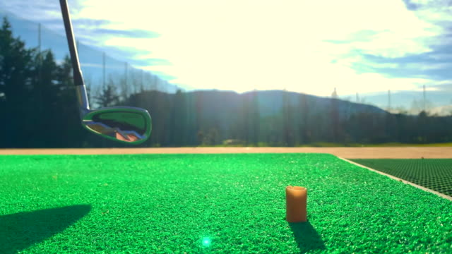 golfer teeing off the golf ball golf from the tee and using golf club epon af-705 on mat on driving range with sunlight in switzerland. - drive ball sports stock videos & royalty-free footage