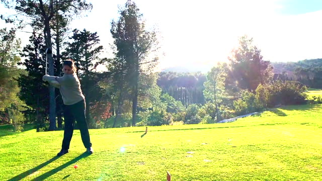 golfer teeing off with driver against sun on golf course - golf swing women stock videos & royalty-free footage