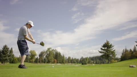 golfer teeing off with driver from tee box - golf shoe stock videos & royalty-free footage