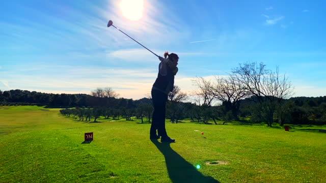 golfer teeing off with golf club driver against sun - 打つ点の映像素材/bロール