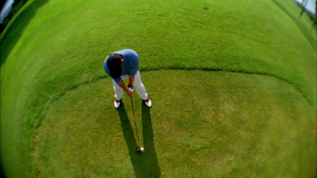 a golfer tees off on a golf course. - teeing off stock videos & royalty-free footage