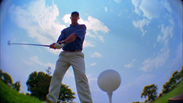 a golfer tees off on a golf course. - golfer stock videos and b-roll footage