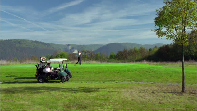 a golfer tees off on a golf course. - golf cart stock videos and b-roll footage