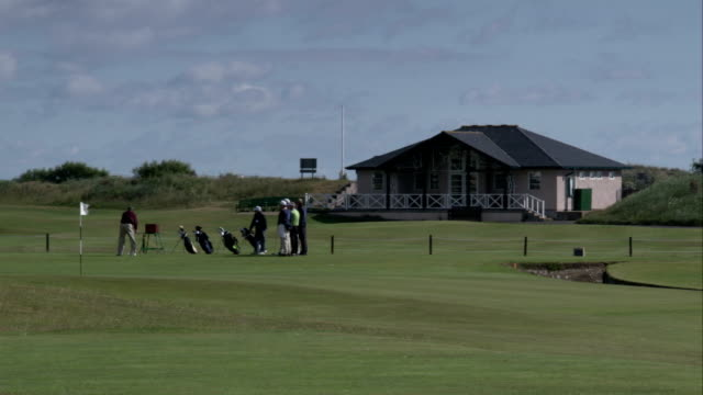a golfer tees off on at st andrews old course, scotland. available in hd. - clubhouse stock videos & royalty-free footage