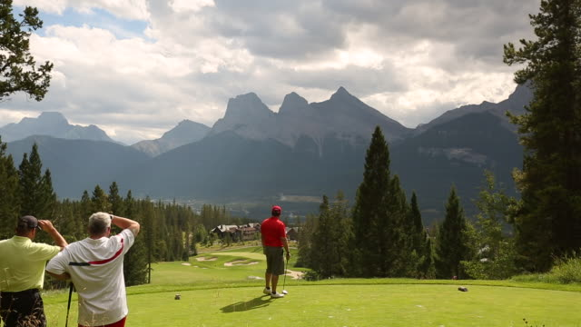 golfer tees off with cloudy mountains in the background - teeing off stock videos & royalty-free footage