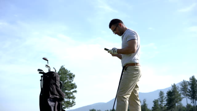 golfer texting on the phone while playing - golf course stock videos & royalty-free footage