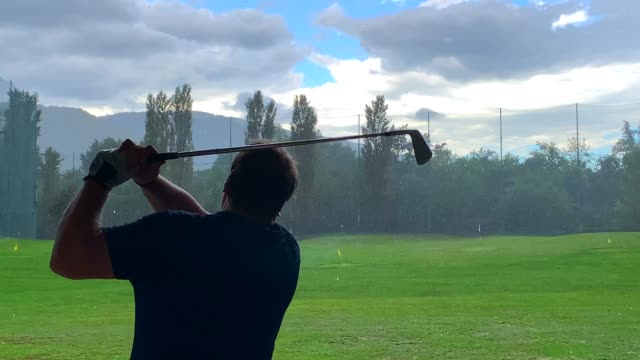 golfer training golf swing on driving range when it's raining - driving range stock videos & royalty-free footage