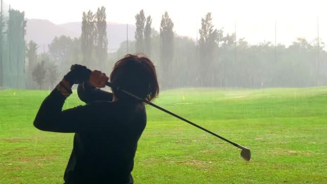golfer training golf swing on driving range when it's raining - golf swing on white stock videos & royalty-free footage