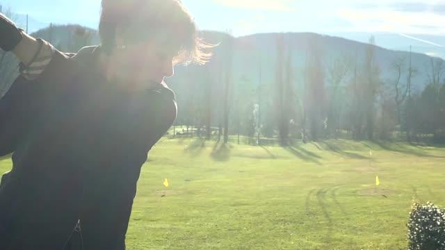 golfer training golf swing on driving range with sunlight - driving range stock videos & royalty-free footage