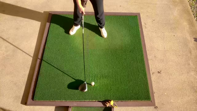 golfer training golf swing with driver on driving range in a sunny day - golf swing on white stock videos & royalty-free footage