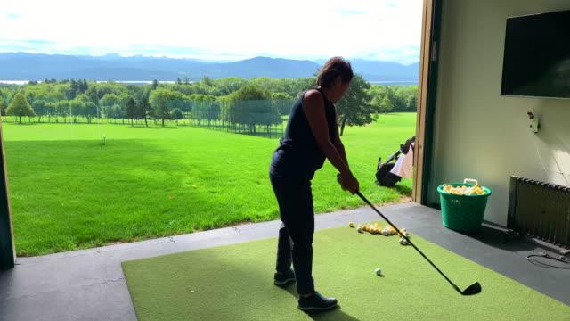 vídeos y material grabado en eventos de stock de golfer training on driving range and hitting slice - swing de golf