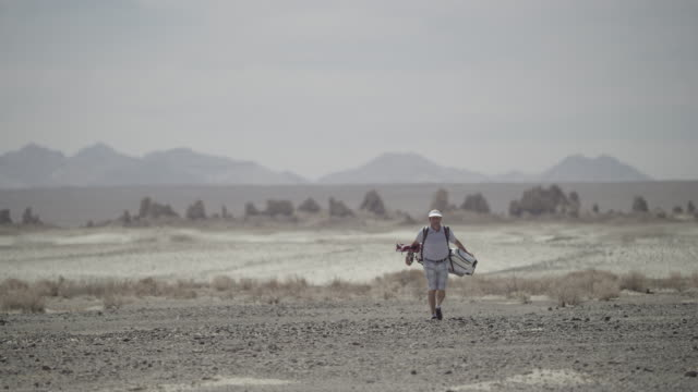 Golfer walks towards camera with Trona Pinnacles in background.