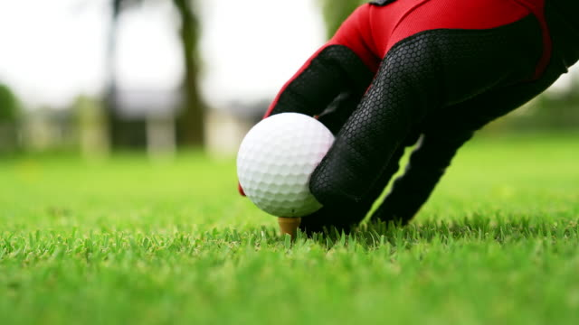 golfer wear red glove putting a ball on a tee. - golf ball stock videos and b-roll footage
