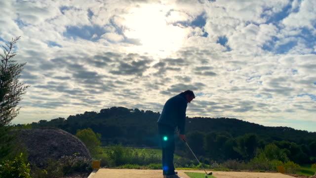 golfer with golf swing against sun and cloudscape - 打つ点の映像素材/bロール