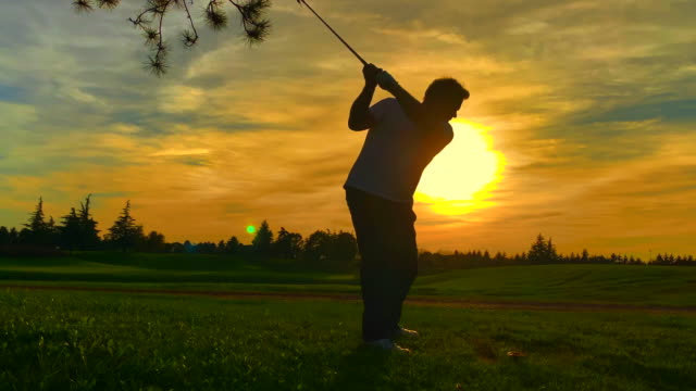 golfer with golf swing against sun in sunset - golf swing silhouette stock videos & royalty-free footage