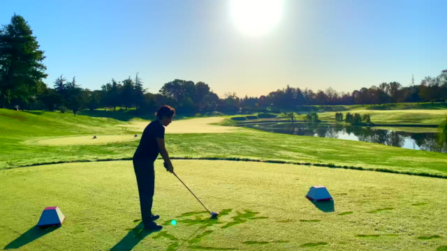 golfer with golf swing against sun in sunset - teeing off stock videos & royalty-free footage