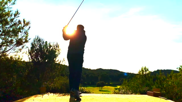 vidéos et rushes de golfer with golf swing against sun - impact
