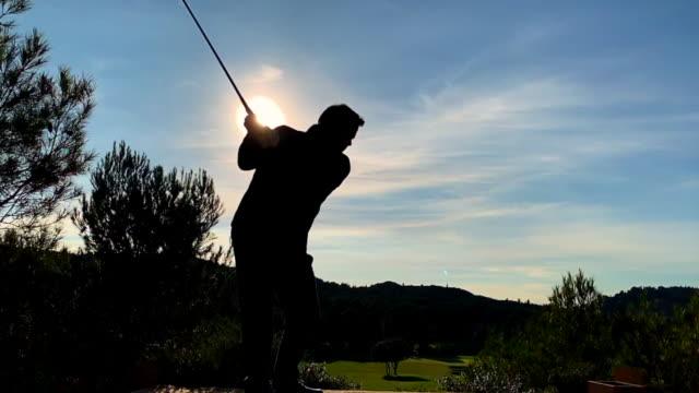 golfer with golf swing against sun - 打つ点の映像素材/bロール