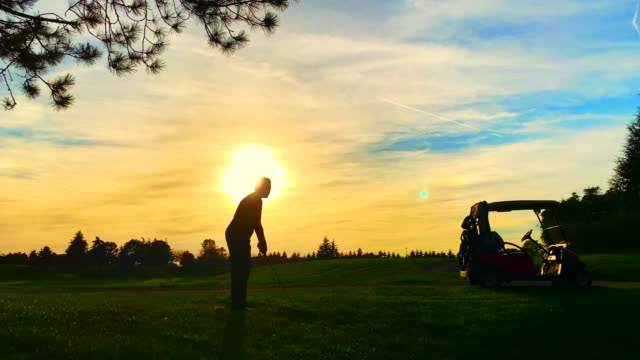 golfer with golf swing and golf cart against sun in sunset - golf cart stock videos & royalty-free footage
