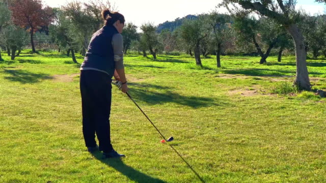 golfer with golf swing in a windy day on the golf course - golf swing women stock videos & royalty-free footage