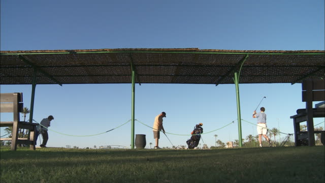 Golfers drive balls at a driving range in Morocco.