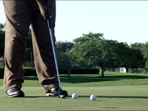 golfer's feet and two golf balls one being putted - golf shoe stock videos & royalty-free footage
