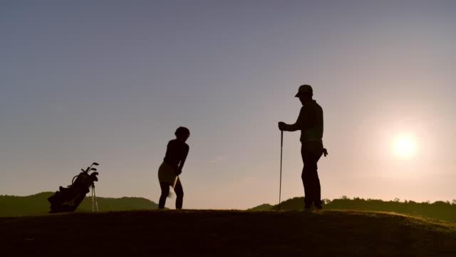 vidéos et rushes de les golfeurs frappent le balayage en été pour détendre le temps, concept de sport. - balle de golf