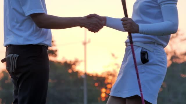 vidéos et rushes de les gens de golfeurs se serrant des mains le terrain de golf dans le jeu de finition d'été. célébration, succès, travail d'équipe, collaboration, soutien, unité, confiance, leadership, pouvoir, compétence, force, amitié, concept. sports cinema - terrain de golf