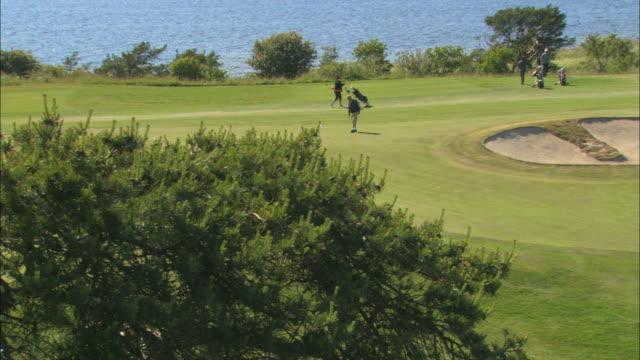 ws cs golfers playing on golf course / visby, nã¤r, ljugarn, gotland, sweden - bandierina da golf video stock e b–roll