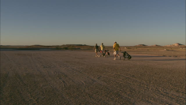 golfers pull their clubs across a course in coober pedy, australia. - coober pedy stock videos & royalty-free footage