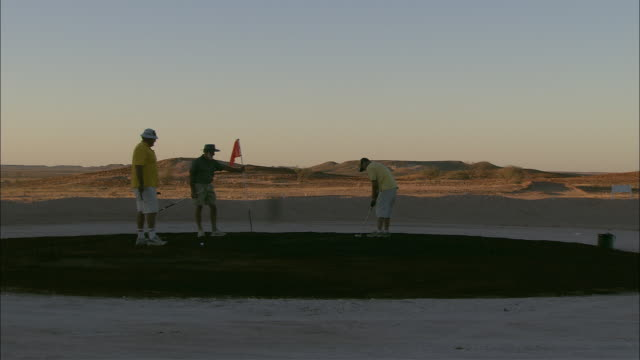 golfers putt on a course in coober pedy, australia. - coober pedy stock videos & royalty-free footage
