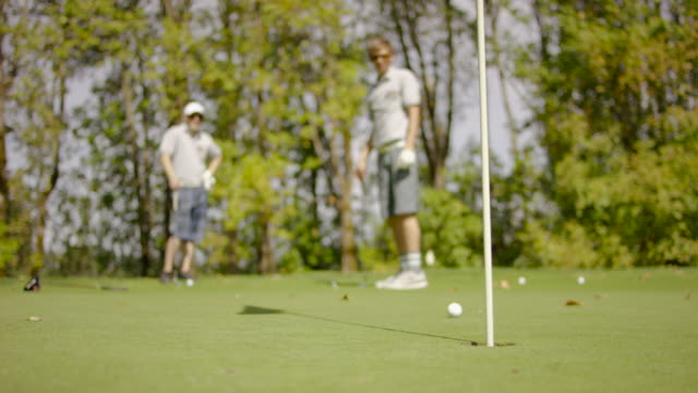 golfers putting on the green of a golf course - golf shoe stock videos & royalty-free footage