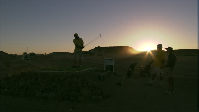golfers tee off during sunset. - tee off stock videos & royalty-free footage