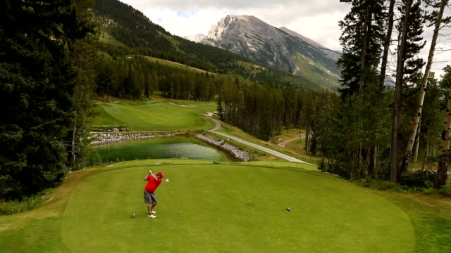 golfers tee off on mountain course - golf course stock videos and b-roll footage