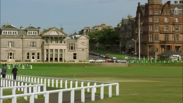 golfers walk to the clubhouse of st. andrews links. - st. andrews scotland stock videos & royalty-free footage