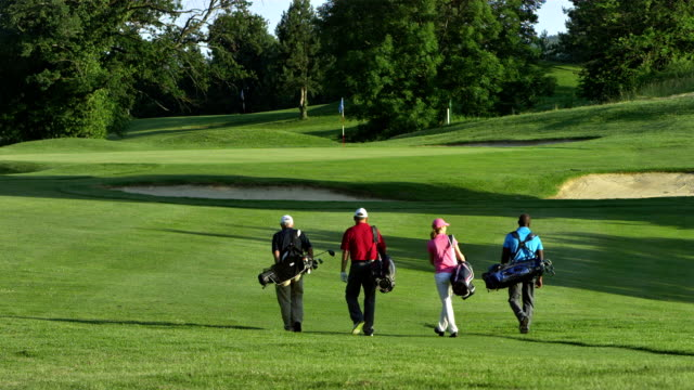 ws golfers walking on the golf course - green golf course stock videos and b-roll footage