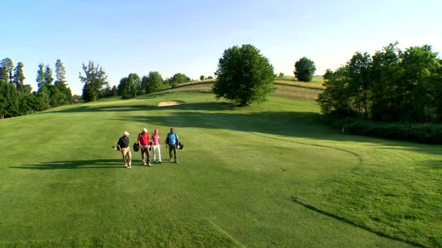 aerial golfers walking on the golf course - golf stock videos & royalty-free footage
