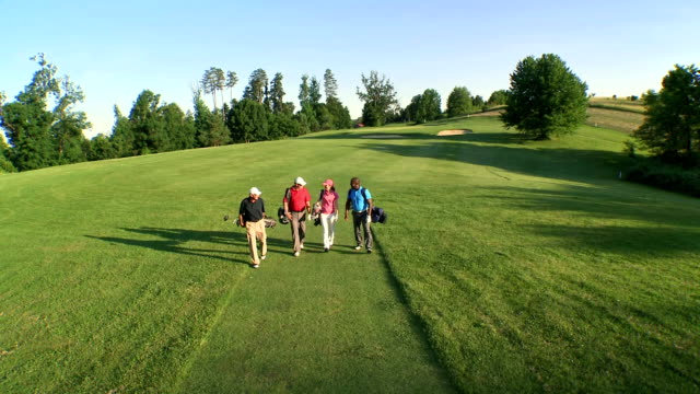 aerial ts golfers walking on the golf course - golf stock videos & royalty-free footage