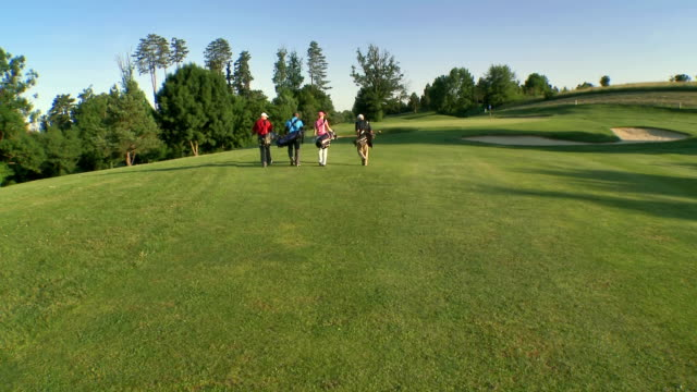 aerial golfers walking on the golf course - green golf course stock videos and b-roll footage