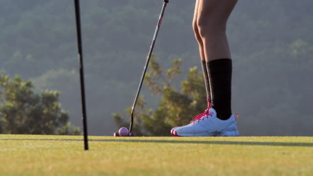 golfers women putting golf ball on the green golf in the summer for relax time.sports cinemagraphs.confidence,power,skill,strength,success.women in sport - golfer stock videos & royalty-free footage
