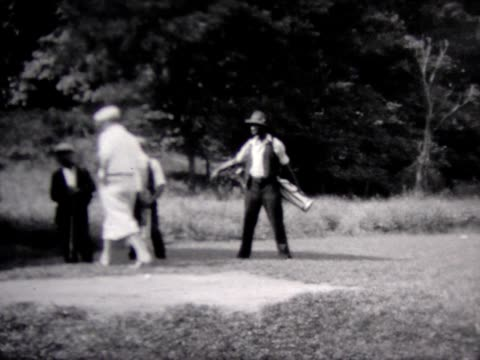 1934 golfing with a black caddy - golf stock-videos und b-roll-filmmaterial