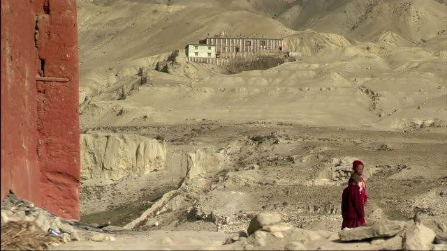 WS Gompa in mountain landscape, two young monks in foreground / Lo Manthang, Mustang, Nepal