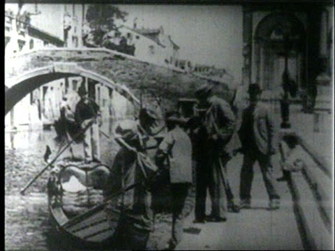 gondola approaches under canoe bridge attendant stands on the embankment looking at the gondola then hooks in the gondola / gondola contains three... - 19th century stock videos & royalty-free footage